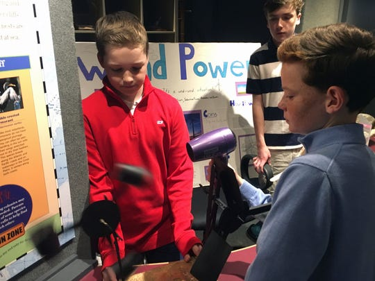 From left, Alexander Williams, William Ginn and Nicolas Pizarro, from the Tatnall School, on Friday use a hair dryer to demonstrate how wind power works at the Delaware Museum on Natural History.
