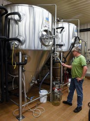 """Brewmaster Chris Laumb checks information on a fermentation tank filled with """"Check Pils,"""" the brewery's special edition beer that will be served during Hockey Day Minnesota events in January. Laumb is shown Wednesday, Nov. 8, at Beaver Island Brewing Co. in St. Cloud."""