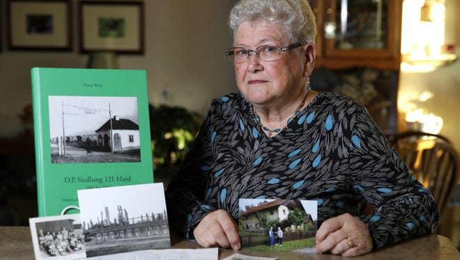 Hermi Krueger of Greenville holds a photo of her mother and herself standing outside the home she was born in while surrounded by photos of her family and images of the refugee camp they lived in in Austria until she was 11.