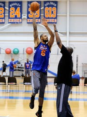 New York Knicks' Tyson Chandler puts up a shot as he works against coach LaSalle Thompson, right, at the team's training camp Tuesday, Oct. 1, 2013.