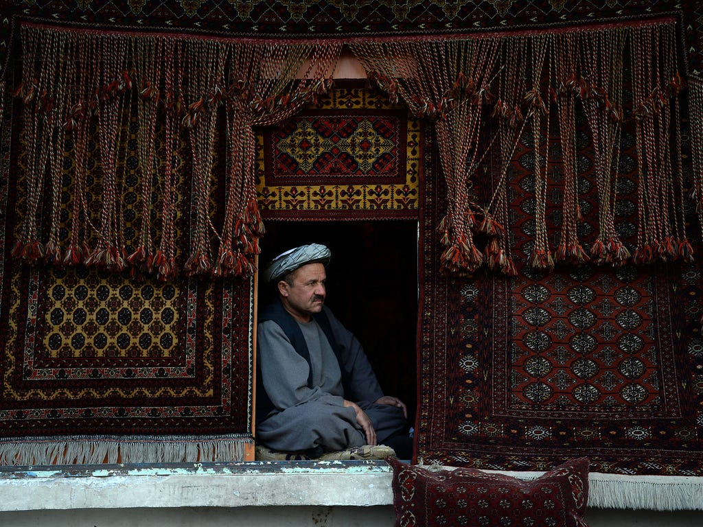 A shopkeeper waits for customers in his carpet shop in the courtyard of the Hazrat-e-Ali Shrine on March 31 in Mazar-i-Sharif, Afghanistan.