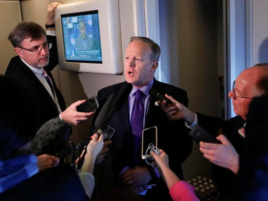 "White House press secretary Sean Spicer speaks to reporters on Air Force One en route to Andrews Air Force Base, Thursday, Jan. 26, 2017, from Philadelphia. Spicer says that taxing imports from Mexico would generate $10 billions a year and ""easily pay for the wall."""