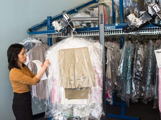 Marina Hung hangs some clothes at Platinum Dry Cleaners in Naples, Fla., on Tuesday, Feb. 28, 2017. In October 2014 Andrew and Lynette Rhodes purchased Platinum Dry Cleaners in Naples from Joe and Sandy Waite, who started Platinum in 1989. Since March 2016, they have purchased four more dry cleaners from Marco Island to Estero.