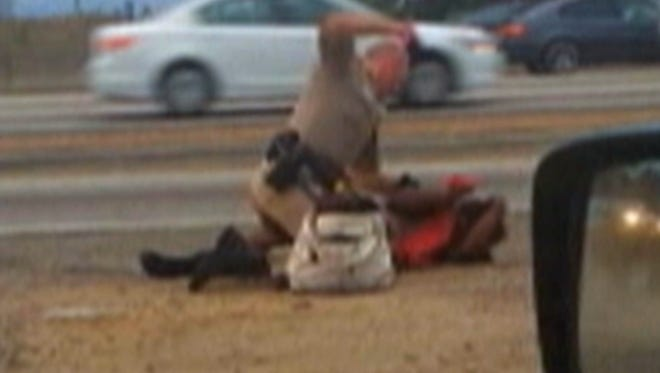 A California Highway Patrol officer straddles a woman while punching her in the head on the shoulder of a Los Angeles freeway, as seen in a screen grab from a video shot July 1, 2014, by motorist David Diaz.