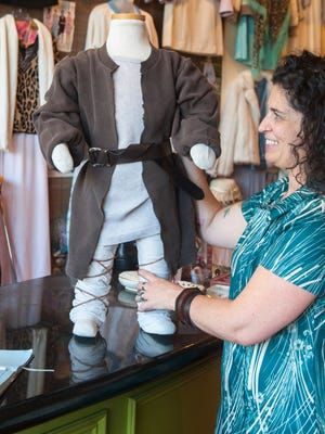Morgan Robinson, owner of Frugal in Collingswood, displays a 'Star Wars'-inspired Jedi outfit that she assembled from items in her store. Robinson says Jedi costumes are particularly easy to do yourself.