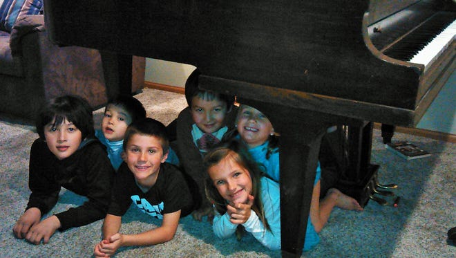 """Grandkids find uses more creative than music for a baby grand piano.  Peering from their """"cave"""" are (from left) Kien, Tommy, Milo, Niko, Ruby and Lola."""