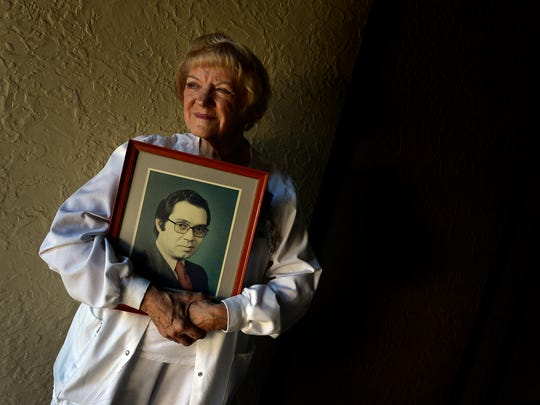 Gwen Edland, 82, holds a 1980 photograph of her late