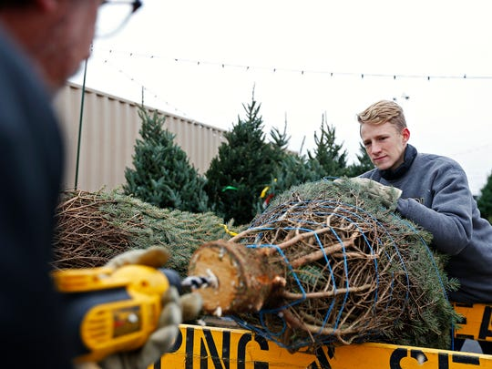 Assistant Scout Master Josh Zahn (left) and his son Noah, 15, drill a hole in the base of a Christmas tree at the stand set up every year by Springfield Boy Scout Troop 24 in Glen Isle Plaza's parking lot in Springfield, Mo. on Nov. 25, 2016.