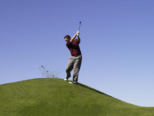 Man standing on hill at golf course, swinging