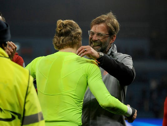 Liverpool manager Juergen Klopp and Liverpool goalkeeper Loris Karius celebrate in front of their side's fans after they won the Champions League quarterfinal second leg soccer match between Manchester City and Liverpool at Etihad stadium in Manchester, England, Tuesday, April 10, 2018. (AP Photo/Rui Vieira)