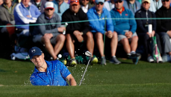 Jordan Spieth hits out of a bunker on the 18th hole during the second round of the 2016 The Masters golf tournament at Augusta National Golf Club.