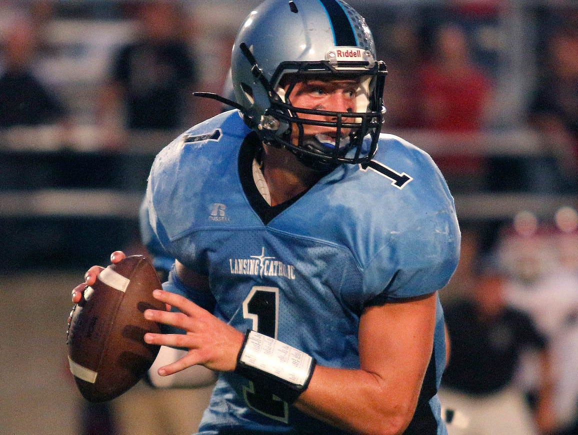 Lansing Catholic quarterback Tony Poljan rolls out against Portland Friday, Sept. 18, 2015, in Holt, Mich.