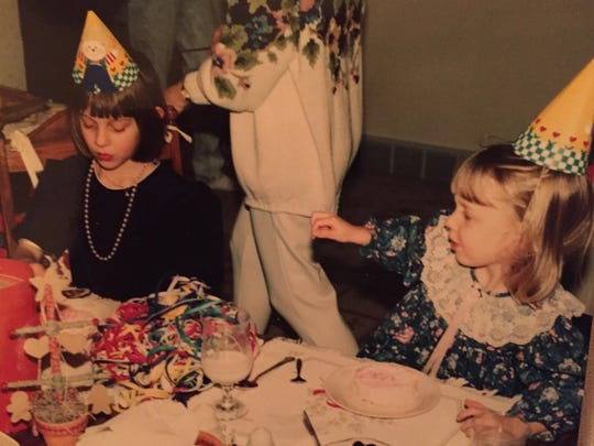 Stephanie Dickrell (age 6) concentrates on her birthday cake, while cousin Emiliy Whipple (then 3 years old) appears to demand her attention, somewhere in Wisconsin in 1992.