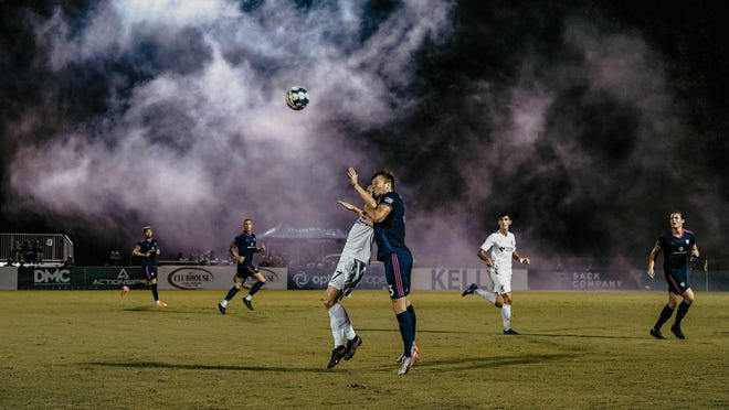 Play continues after smoke from the supporters' section clouds the field following a goal by Tormenta FC, and Stefan Mueller (3) rises high for a header against Union Omaha on Sept. 11, 2020.