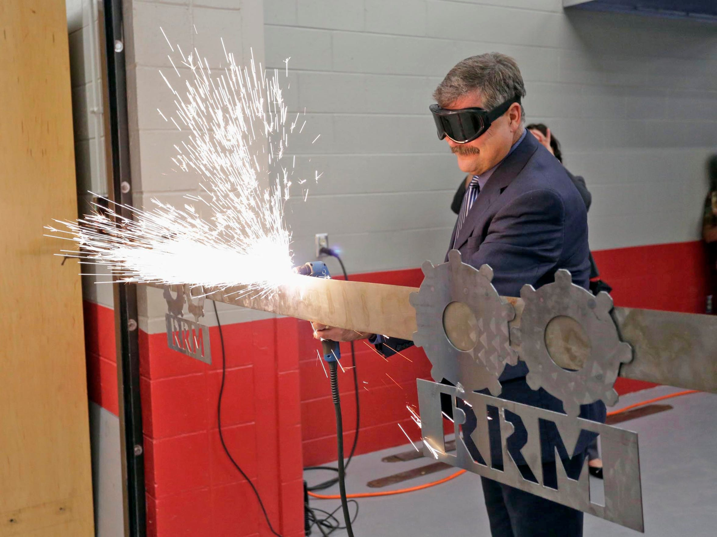 "Joseph Sheehan, then superintendent of the Sheboygan Area School District, cuts through a metal ""ribbon"" using a plasma cutter in October 2016 at the Red Raider Manufacturing Kohler/Johnsonville Advanced Technology Centers at Sheboygan South High School. Red Raider Manufacturing is a program within the city's two comprehensive high schools that exposes students to manufacturing, one of several efforts to hang onto talent in the county as businesses face labor shortages. Sheehan is now executive director of the Sheboygan County Economic Development Corp."