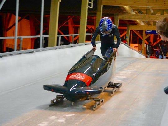 Noah Crofton (16) begins a bobsled training run in