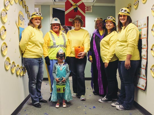 """City Hall staff dressed as Minions stand with Amaya Robinson who dressed as Elsa from """"Frozen"""" Monday morning."""