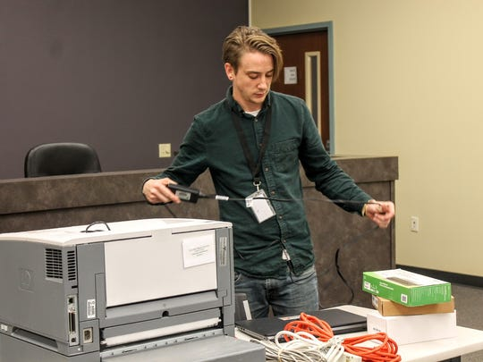 Dylan Garmon of Automated Election Services, sets up computers at the Tularosa Public Facility Courtroom, 609 St. Franics Dr. Monday afternoon.