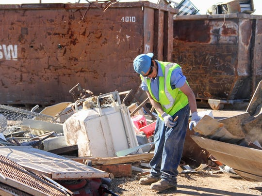 A La Luz Convenience Center employee sorts through scrap metal at the La Luz collection site Friday afternoon.