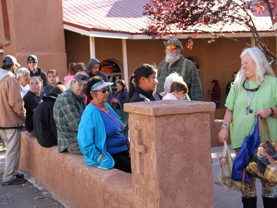 Residents line up outside the Our Lady of the Light Catholic Church Food Pantry Tuesday.