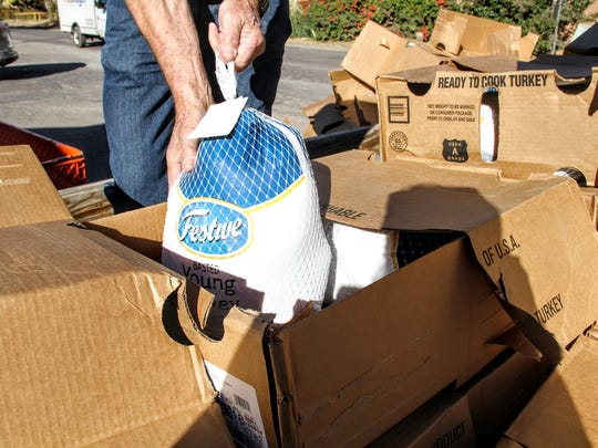 A food pantry volunteer unloads turkeys outside the Our Lady of the Light Catholic Church food pantry Tuesday.