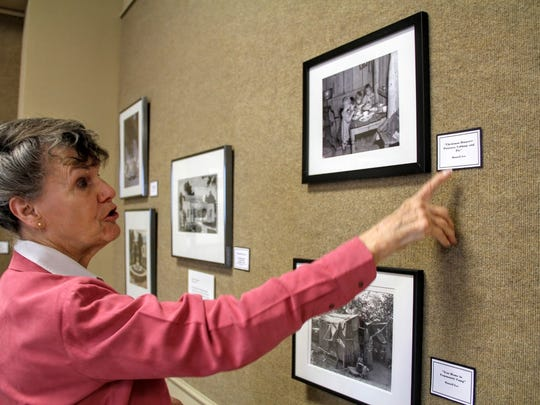 Tularosa Basin Museum of History docent Donna Doyle Milburn discusses a photograph from their New Deal Federal Arts Project art exhibit.