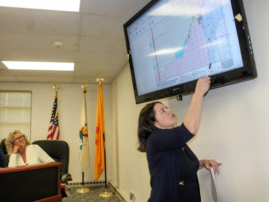 Sen. Martin Heinrich's spokeswoman Dara Parker points at a map showing White Sands National Monument's territory at the Dec. 9 county commission meeting.