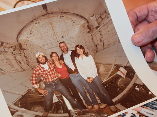 Arthur Mcintosh holds up an old photograph of himself and colleagues when he used to work for NASA.