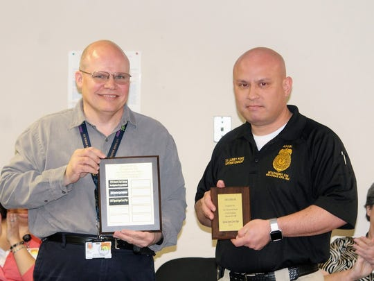 CYFD County Officer Manager for both Lincoln and Otero counties Larry Wisecup presents an award of recognition to Special Agent Larry Pope with Special Forces at Holloman Air Force Base for his work with children Tuesday in honor of Law Enforcement Appreciation Month.