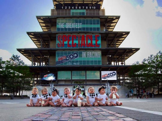 The eight babies born weeks apart pose for a photo at the Indianapolis Motor Speedway.