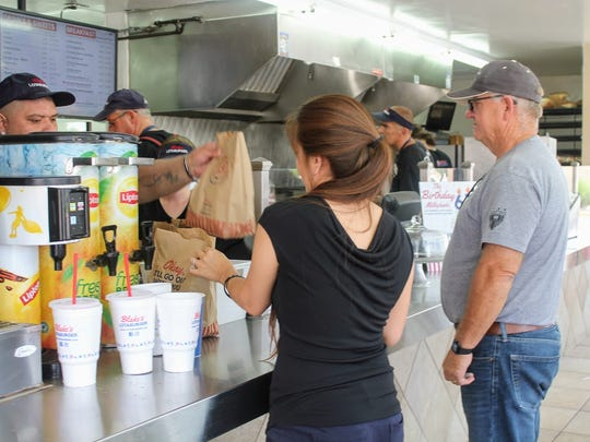 Customers receive their Lotaburgers Tuesday afternoon at Alamogordo's Blake's Lotaburger, 1320 N. White Sands Blvd.