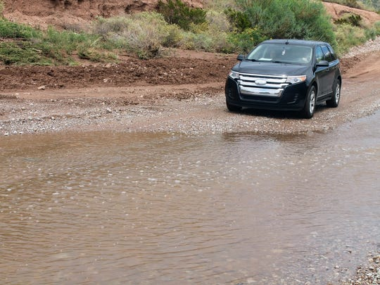 A car tries to drive through a low water crossing at Section Road in La Luz Tuesday afternoon. The road dealt with extreme flooding Monday.