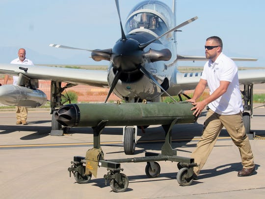 A maintenance crew member shows off how fast and simple it is to rearm an A-29 Super Tucano during Holloman's light attack experiment Wednesday.