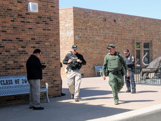 Law enforcement officers walk the perimeter of Alamogordo
