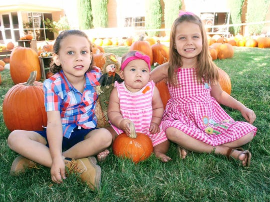 From left to right, Andrew Sackett, Aviana Stafford and Leticia Sackett sit for a photo at the Grace United Methodist Church pumpkin patch Monday afternoon.