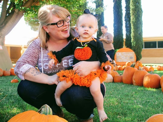Aeris Bigbee sits on her mom's lap at the Grace United Methodist Church pumpkin patch Monday afternoon.
