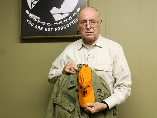 Stet Reid stands with his uniform he wore during his