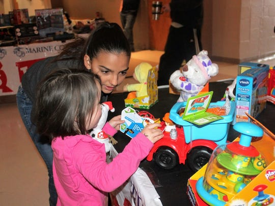 A young volunteer helps a child pick out a toy Saturday