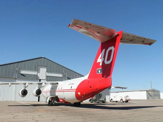 A Neptune BAe-146 sits in front of a hangar at the Alamogordo-White Sands Regional Airport which has been modified to fit the new slurry bomber. The cross-shaped entrance on top of the hangar is to fit the tail of the new air tanker.
