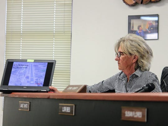 County Commissioner Janet White assists with a PowerPoint presentation on the Alamogordo-White Sands Regional Airport at the county's regular meeting March 8.