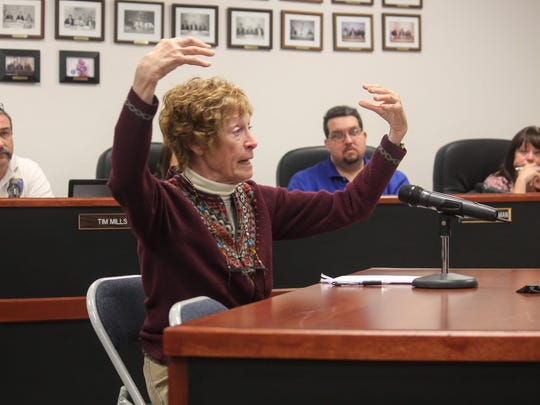 County resident Maxine Laplace demonstrates how firework embers shower down on her horses and other livestock animals at the county's public hearing on fireworks Wednesday.