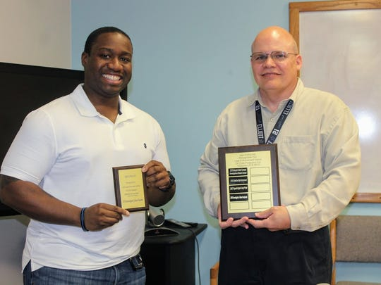 Holloman Air Force Base Security Forces officer Julian Benjamin, left, accepts an award from CYFD County Office Manager for both Lincoln and Otero counties Larry Wisecup, right, Tuesday for his his efforts in serving children in Otero County.