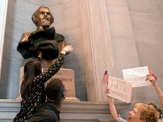A protester tries to cover the bust of Nathan Bedford