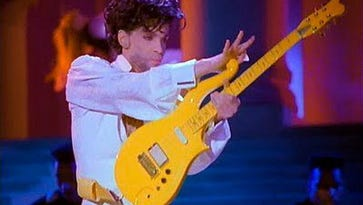 Prince playing his Yellow Cloud electric guitar in the 1990s.