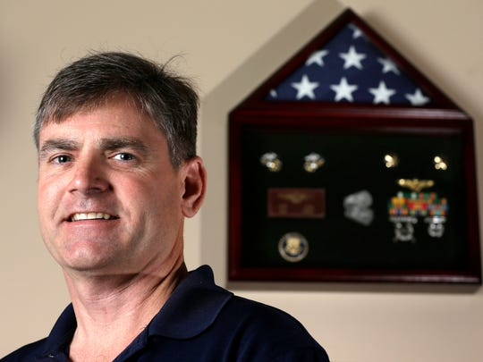 In this Wednesday, Dec. 14, 2016, photo retired Marine David Kirk poses next to a display of his military medals at his home in Friendswood, Texas. Kirk, who has flown former President George W. Bush as well as vice presidents, failed a polygraph after 12 hours of highly adversarial questioning over two days when applying for a job with Customs and Border Protection. (AP Photo/David J. Phillip)