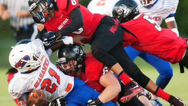 South Fort Myers High School's Jeshaun Jones, top, and Howard Wehrenberg, middle, tackle Cape Coral High School's Isaac Washington during play Friday at South Fort Myers High School.
