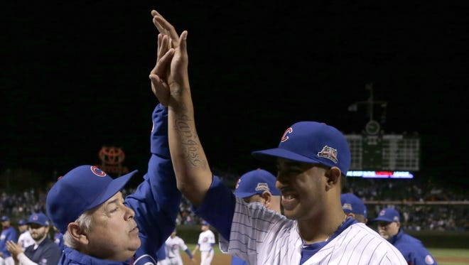 Chicago Cubs manager Rick Renteria, left, celebrates the Cubs' 3-1 win over the St. Louis Cardinals with relief pitcher Hector Rondon, after a baseball game Wednesday, Sept. 24, 2014, in Chicago. (AP Photo/Charles Rex Arbogast)