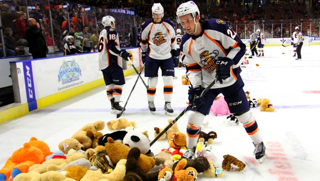 Greenville Swamp Rabbits team member Paul Zanette helps to pile up stuffed animals that were thrown on to the ice after their first goal scored in the game against the South Carolina Sting Rays at the Bon Secours Wellness Arena on Friday night, December 2, 2016. The stuffed animals will be given to Toys for Tots.