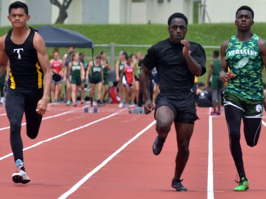 Tiyan senior Matt Wong, left, runs alongside Zama's Jaelen Baker, center, and Kubasaki's Mahlik Francis in the 100-meter dash April 8 in the 12th Mike Petty Memorial Meet at Camp Foster on Okinawa. Wong edged out both competitors for the gold.