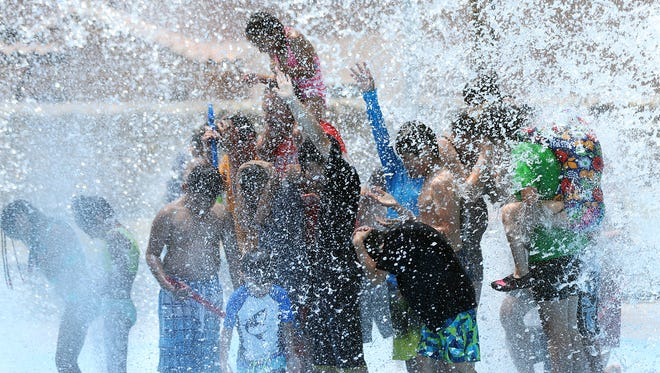 Children wait to get dowsed by a large bucket of water that tips over when full at the Marty Robbins Spray Park at 11600 Vista Del Sol Drive last year.